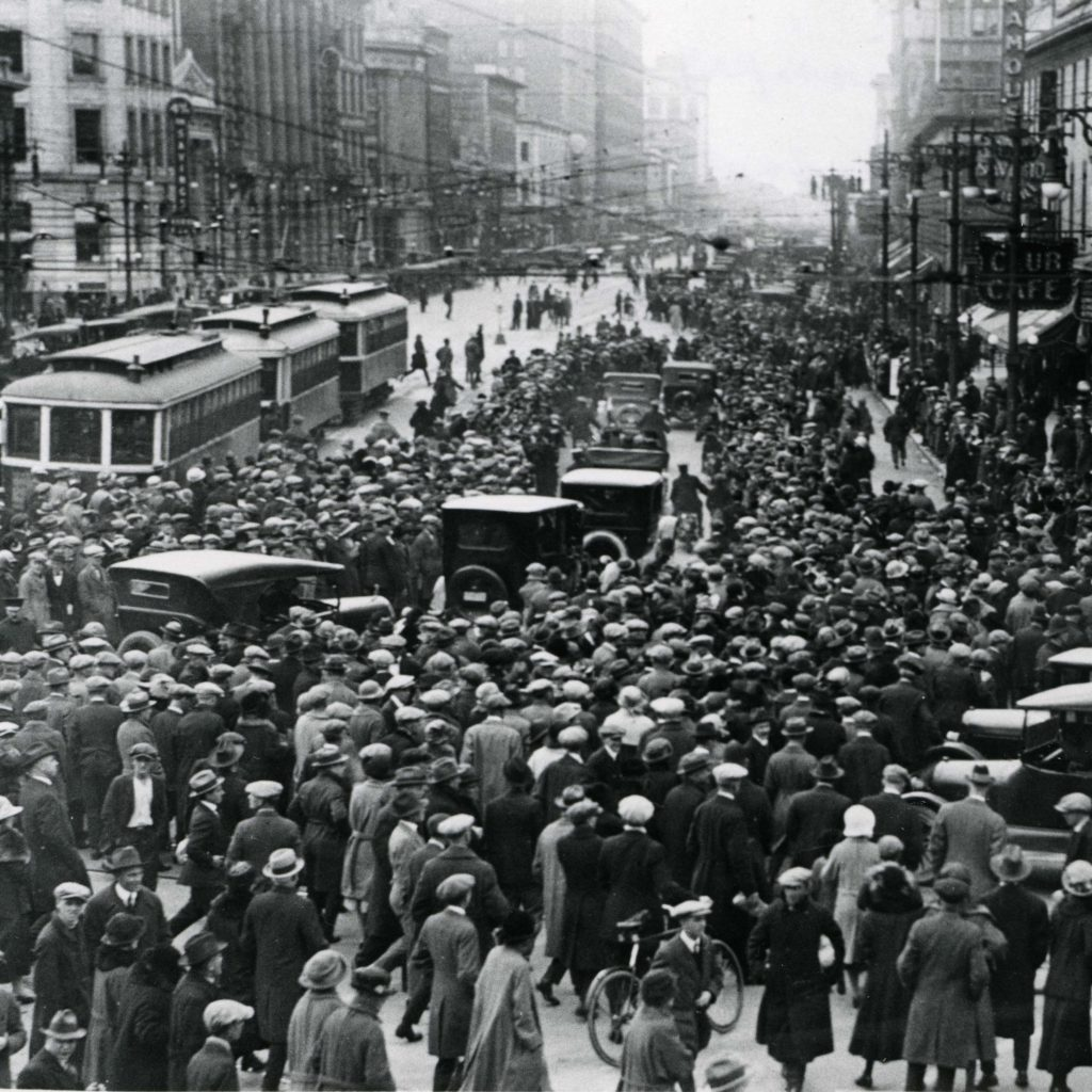 Black and white photograph showing crowds of people in downtown Winnipeg during the Winnipeg General Strike. automobiles and streetcars move between the crowds. Source: University of Manitoba Archives & Special Collections.