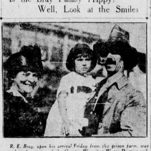 "A photograph of Roger Bray with his wife and a young child. The headline reads: ""Is the Bray Family Happy? Well, Look at the Smiles."" and the photograph is captioned: ""R.E. Bray, upon his arrival Friday from the prison farm, was greeted at the station of the Greater Winnipeg Water District railway by his wife and Katie, his eldest daughter."" Source: University of Manitoba Libraries"